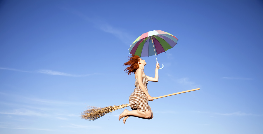 Young red-haired witch on broom flying in the sky with umbrella